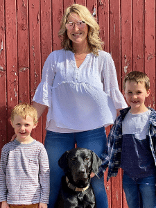 Emily stands with her two children and dog in front of a red barn